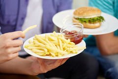 Close up of male hands with fast food on plates Royalty Free Stock Image