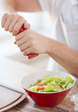 Close up of male hands flavouring salad in a bowl Stock Photos