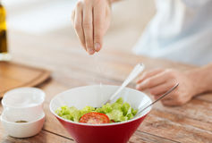 Close up of male hands flavouring salad in a bowl Royalty Free Stock Images