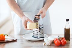 Close up of male hands grating cheese Stock Image
