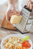 Close up of male hands grating cheese over pasta Royalty Free Stock Photography