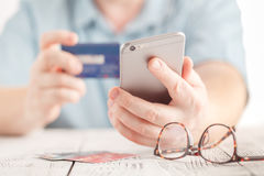 Close up male hands holding credit card and using mobile smart phone for online shopping Royalty Free Stock Photo