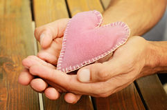 Close up on male hands holding a heart. Love, handmade, valentine concept Stock Images