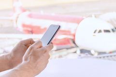 Close-up, male hands holding a mobile phone,  airport blurry background. royalty free stock photography