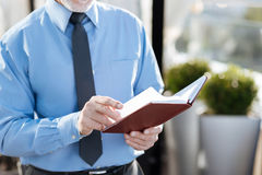 Close up of male hands that holding notebook. Turn next page. Grey haired man paging his notes and checking timetable while going to make new appointment Royalty Free Stock Image