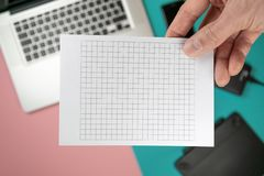 Close up male hands holding paper blank for design paper. On worktable background royalty free stock image