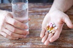 Close up of male hands holding pills and water. Healthy lifestyle, medicine, nutritional supplements and people concept - close up of male hands holding pills Royalty Free Stock Photo