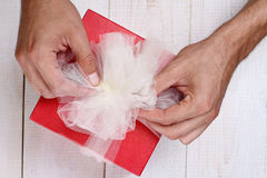 Close up on male hands holding red present with white Ribbon . Gift box packaging. Birthday, New year, Valentine's Day, 8 march, C Royalty Free Stock Photo