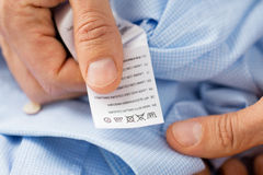 Close up of male hands holding shirt and label Stock Images