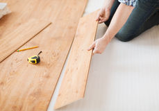 Close up of male hands intalling wood flooring Stock Photos