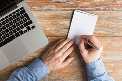 Close up of male hands with laptop and notebook Royalty Free Stock Photo