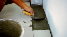 Close up male hands laying ceramic floor tiles stock video footage