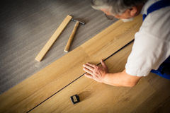 Close up of male hands  lying parquet floor board. DIY, repair, building and home concept - close up of male hands lying parquet floor board/laminate flooring ( Stock Photos