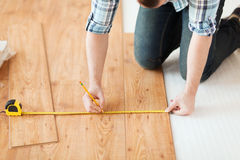 Close up of male hands measuring wood flooring. Repair, building and home concept - close up of male hands measuring wood flooring Stock Photos