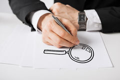 Close up of male hands with pen drawing lens Stock Photo