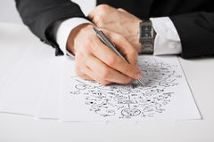 Close up of male hands with pen drawing scheme Stock Photos
