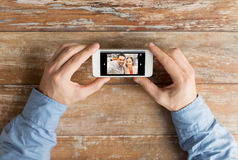 Close up of male hands with photo on smartphone Stock Photos
