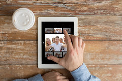 Close up of male hands with photo on tablet pc Stock Image