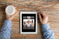 Close up of male hands with photo on tablet pc Royalty Free Stock Photos