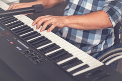 Close up of male hands while playing on electric piano Stock Photo