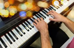 Close up of male hands playing piano. Music, people and instruments concept - close up of male hands playing piano over lights Royalty Free Stock Image