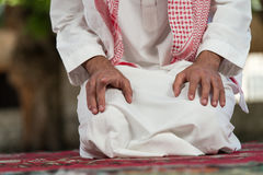 Close-Up Of Male Hands Praying In Mosque. Young Muslim Man Making Traditional Prayer To God While Wearing A Traditional Cap Dishdasha stock photography