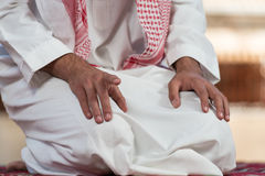 Close-Up Of Male Hands Praying In Mosque. Young Muslim Man Making Traditional Prayer To God While Wearing A Traditional Cap Dishdasha royalty free stock photos