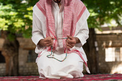 Close-Up Of Male Hands Praying With Rosary. Young Muslim Man Making Traditional Prayer To God While Wearing A Traditional Cap Dishdasha stock images