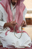 Close-Up Of Male Hands Praying With Rosary. Young Muslim Man Making Traditional Prayer To God While Wearing A Traditional Cap Dishdasha stock photo
