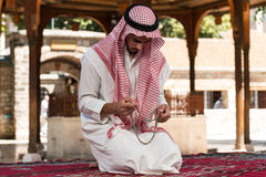 Close-Up Of Male Hands Praying With Rosary. Young Muslim Man Making Traditional Prayer To God While Wearing A Traditional Cap Dishdasha royalty free stock photos