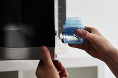 Male hands putting a baby bottle with water into a microwave. Close up of male hands putting a baby bottle with water into a microwave Stock Photo