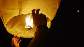 Close-up of male hands releasing Chinese lanterns in the night sky stock footage