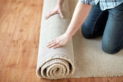 Close up of male hands rolling carpet. Repair, building and home concept - close up of male hands rolling carpet Stock Images