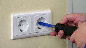Close up of male hands with screwdriver unscrew electrical outlet. Close up of male hands with screwdriver unscrew electrical socket outlet on wall stock footage