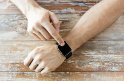 Close up of male hands setting smart watch. Business, technology and people concept - close up of male hands setting smart watch at home Stock Photography