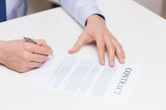 Close up of male hands signing contract document. People, business and paperwork concept - close up of male hands signing contract document at office Stock Photography