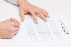 Close up of male hands signing contract document. People, business and paperwork concept - close up of male hands signing contract document at office Royalty Free Stock Images