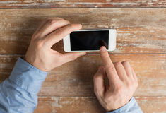 Close up of male hands with smartphone on table Stock Image