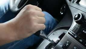 Close-up of male hands switching automatic gearbox in expensive car, driver. Slow motion hd footage stock video