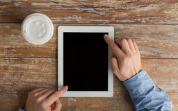 Close up of male hands with tablet pc and coffee Stock Images