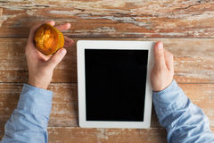 Close up of male hands with tablet pc and muffin Stock Photography