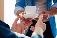 Close up of male hands that taking care. Good attitude. Kind son standing opposite his father and holding cup with tea, wearing casual clothes Royalty Free Stock Image