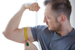 Close up of male hands with tape measuring bicep. Sport, fitness, lifestyle, bodybuilding and people concept - close up of male hands with tape measuring bicep Stock Images