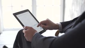 Close-up of male hands touching digital tablet