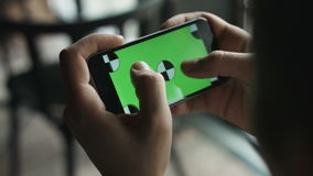 Close-up of male hands touching green screen on mobile phone. Guy zoom in and zoom out picture.  Green screen Chroma Key. Close-up of male  hands touching green stock footage