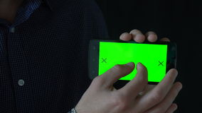 Close-up of male hands touching of smartphone. Green screen Chroma Key. Close up. Tracking motion. Vertical. pants. - stock video