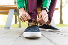 Close up of male hands tying shoe laces on street Royalty Free Stock Images