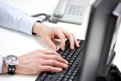 Close up of male hands typing on computer keyboard Stock Image