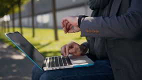 Close up. Male hands typing on computer keyboard. Outdoors. Young businessman sitting on the bench and uses laptop. Man stock footage