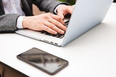 Close up of male hands typing on laptop computer. On a table with mobile phone outdoors Royalty Free Stock Photos
